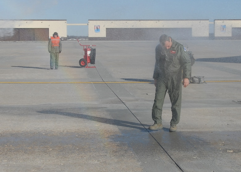 """DOUSED! Col Robert """"Herm"""" Leeker, 131st Bomb Wing Commander, Missouri Air National Guard, is doused with a fire hose in honor of his final B-2 flight at Whiteman Air Force Base on February 25.  (U.S. Air Force Photo by Master Sergeant Mary-Dale Amison.  RELEASED)"""