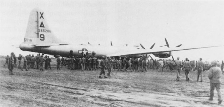 """Dinah Might,"" the first crippled B-29 to make an emergency landing on Iwo Jima during the fighting, is surrounded by Marines and Seabees on 4 March 1945.