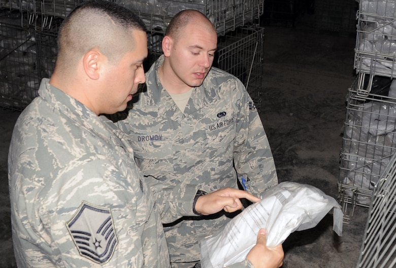 Master Sgt. Alex Brown checks over inventory numbers with Senior Airman Alex Dromov in the supply warehouse for the 380th Expeditionary Logistics Readiness Squadron at a non-disclosed base in Southwest Asia on March 6, 2010. Both work in the ?Desert Depot,? otherwise known as the base supply store and both are material management Airman deployed with the 380th ELRS. (U.S. Air Force Photo/Master Sgt. Scott T. Sturkol)