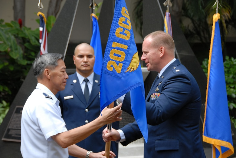 Major Gen. Darryl Wong, HIANG Commander, hands the unit the unit 'colors' over to Lt. Col. Gregory Schrivner during the 201st's activation ceremony, Mar. 7. (U.S. Air Force photo, A1C Orlando Corpuz)