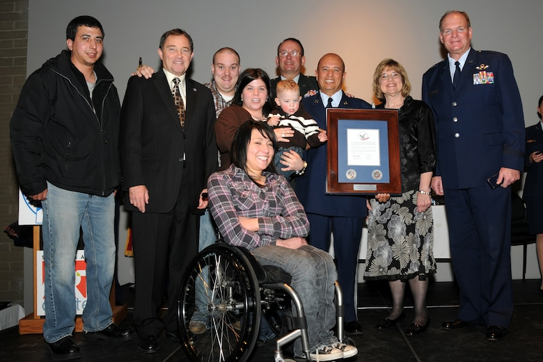 Tech. Sgt. Pascual Ramirez, 151st Logistics Readiness Squadron, and his family pose with their Hometown Heroes plaque at a ceremony March 5 at the Salt Lake Arts Center. The 151st Air Refueling Wing hosted a Hometown Heroes Salute recognizing members of the Utah Air National Guard who have deployed for more than 30 consecutive days since 9/11. Utah Gov. Gary R. Herbert; Maj. Gen. Brian L. Tarbet, the Adjutant General; and General David M. Hooper, Assistant Adjutant General for Air, presented the awards to approximately 80 members of the Utah ANG during the event. U.S. Air Force Photo by Staff Sgt. Emily Monson (RELEASED)