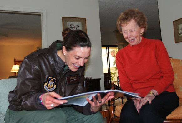 Women's Airforce Service Pilot, Mrs. Margo deMoss (right) shows Capt. Jennifer Phillips candid photos in a WASP reunion program.  Captain Phillips, who is a KC-135 pilot with the 336th Air Refueling Squadron at March Air Reserve Base, Calif., visited de Moss at her home near the base, March 5, 2010.  (U.S. Air Force photo/Megan Just)
