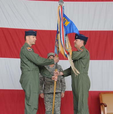 Lt. Col. David Garfield, 944th Operations Group commander, passes the 69th Fighter Squadron guidon to Lt. Col. Steve Speckhard, 69th FS commander, during the squadron's activation ceremony March 6 where the pilots of the 301st Fighter Squadron symbolically changed their patch to the 69th FS. The 301st FS, which traces its roots to the Tuskegee Airmen of World War II, will continue its legacy with the next generation aircraft, the F-22 Raptor, at Holloman Air Force Base, N.M., as a Reserve associate unit. The 69th FS pilots will continue their reserve associate pilot training program with the 56th Fighter Wing here at Luke. (U.S. Air Force photo/Tech. Sgt. Susan Stout)