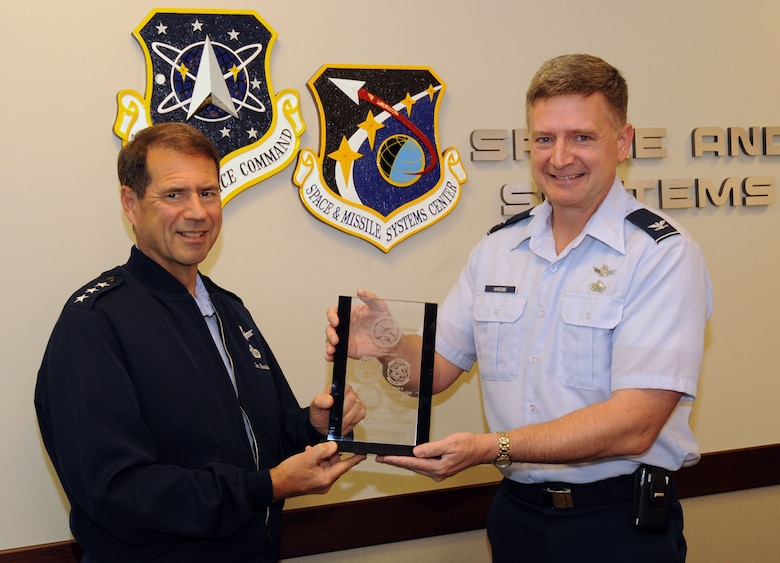 Lt. Gen. Tom Sheridan, SMC commander, receives a commemorative plaque from Col. William Harding, Military Satellite Systems Wing deputy commander, March 8.  The plaque was presented to SMC by The Boeing Corporation to mark the completion of the Wideband Global SATCOM Block I satellites. (Photo by Lou Hernandez)