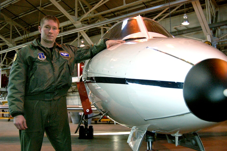 """Capt. Chris """"NASA"""" Thiesing, standardization and evaluation liaison and C-21 pilot for the 118th Airlift Squadron, stands next to a C-21 in the main hangar at Bradley Air National Guard Base, East Granby, Conn. Thiesing originally joined the Conn. Air National Guard as an enlisted Airman working in intelligence and became a pilot after achieving a bachelor's degree. Thiesing said he wants guardsmen to know that being a traditional guardsman affords you the opportunity to get an interview to become a pilot if you meet the eligibility requirements. (U.S. Air Force photo by Tech. Sgt. Joshua Mead)"""