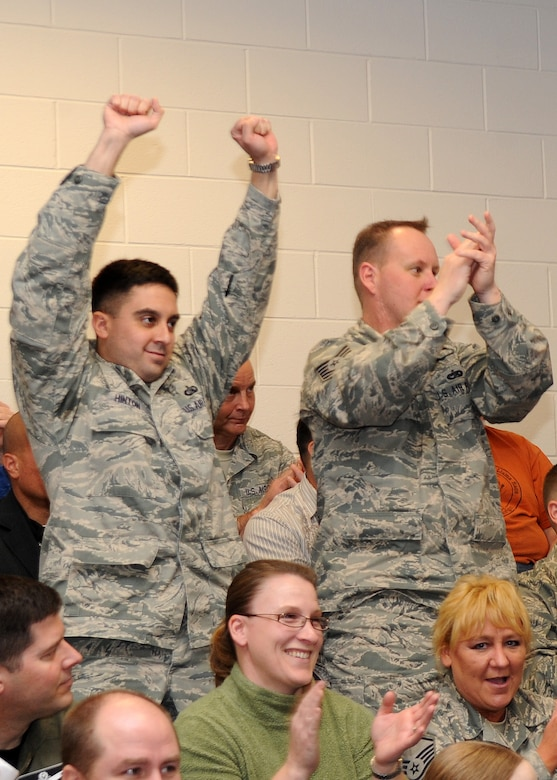 BUCKLEY AIR FORCE BASE, Colo. -- Maj. Ben Hinton and Tech. Sgt. Ronald Brown, 460th Space Wing Command Post, cheer during the Operational Readiness / Unit Compliance Inspection outbrief March 10. Team Buckley passed the no-notice ORI/UCI with a satisfactory rating. ( U.S. Air Force Photo by Airman 1st Class Marcy Glass )