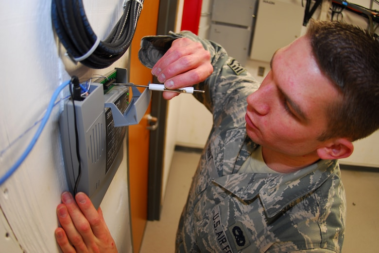 BUCKLEY AIR FORCE BASE, Colo. -- Staff Sgt. Corey Frint, 460th Space Communications Squadron infrastructure system technician, performs a phone install March 9. The system is instrumental to ensuring communications closet security.(U.S. Air Force photo by Tech. Sgt. Anika Williams)