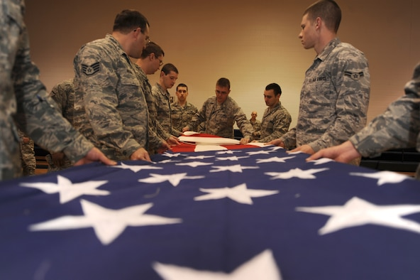 WHITEMAN AIR FORCE BASE, Mo., - Members from the 509th Communications Squadron ceremoniously fold a garrison-size flag inside the fitness center, here, March 9, 2010.  Capt.  Jason Mayne, 509th Communications Squadron Officer, currently deployed to Kuwait, rescued the two flags from disposal for display at the new 509th CS consolidated building in November 2010. (U.S. Air Force photo/Senior Airman Jessica Mae Snow) (Released)