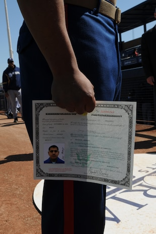 Cpl. Jorge Martinez, Marine Attack Squadron 214 airframer, stands with his certificate of citizenship at the Peoria Sports Complex in Peoria, Ariz., March 10, 2010. Both he and Cpl. Marvin Medeiros, Headquarters and Headquarters Squadron food service specialist, received their certificates during a ceremony before a San Diego Padres and Milwaukie Brewers game. Martinez and his family immigrated to the U.S. from Mexico in 1986, while Medeiros emigrated from Peru in 2000. Both Marines are based at the Marine Corps Air Station in Yuma, Ariz.