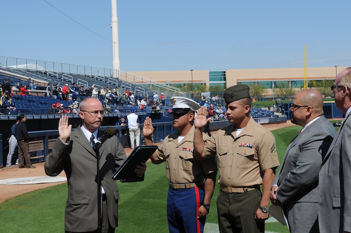 Cpl. Jorge Martinez, left, Marine Attack Squadron 214 airframer, and Cpl. Marvin Medeiros, Headquarters and Headquarters Squadron food service specialist, recite the oath of citizenship at a ceremony at the Peoria Sports Complex in Peoria, Ariz., March 10, 2010. Martinez and his family immigrated to the U.S. from Mexico in 1986, while Medeiros emigrated from Peru in 2000. Both Marines are based at the Marine Corps Air Station in Yuma, Ariz.