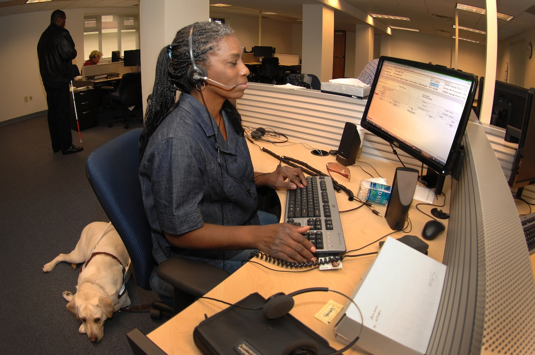 Beverly Redic employs Job Access with Speech, an interactive screen reader with text-to-speech capabilities to help a customer at the new Telephone Consolidated Operatior Center at Travis. (U.S. Air Force photo/Nan Wylie)