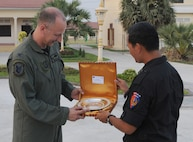 PHNOM PENH, Kingdom of Cambodia -- Brig. Gen. Hun Manet (right), Royal Cambodian Armed Forces National Counter-Terrorism Special Forces commander, hands a memento Col. Robert Toth, 353rd Special Operations Group commander, after the closing ceremonies of a combined training exercise here Feb. 24 Airmen from the 353rd Special Operations Group deployed here Feb. 21-24 to support a training exercise between U.S. Army Special Forces and Royal Cambodian Armed Forces National Counter-Terrorism Special Forces. (U.S. Air Force photo by Tech. Sgt. Aaron Cram)