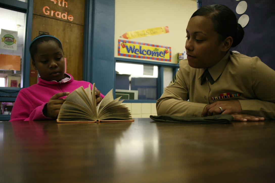 ::r::::n::Cpl. Chantal A. Jarmond, a supply clerk with Marine Tactical Air Command Squadron 28, reads a book with Tykeriah Reeves, a fourth-grade student at Roger Bell Elementary School, March 11, as part of the Adopt-A-School program. The program allows Cherry Point units to partner with local schools.::r::::n::