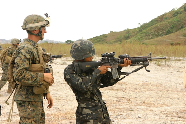 A Republic of the Philippines Marine fires rounds down range as a U.S. Marine with Battalion Landing Team 2nd Battalion, 7th Marines (BLT 2/7), 31st Marine Expeditionary Unit (MEU), instructs him during a small-arms shoot, March 13.  The small-arms shoot was part of bilateral training being conducted during exercise Balikatan 2010 (BK '10).