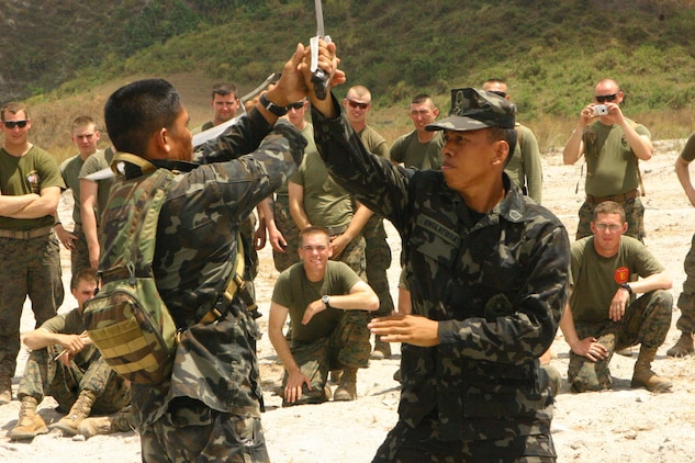 Tech Sgt. Manuel S Prado Jr. (left), a chief master instructor, and Staff Sgt. Carlito M Englatiera Jr. (right), a martial arts instructor, both with the Republic of the Philippines Marine Corps Martial Arts Program demonstrate Pekithtirsia defense moves to U.S. Marines with Battalion Landing Team 2nd Battalion, 7th Marines (BLT 2/7), 31st Marine Expeditionary Unit (MEU), March 13.  The martial arts class was part of bilateral training being conducted during exercise Balikatan 2010 (BK '10). (Official Marine Corps photo by Cpl. Michael A. Bianco)