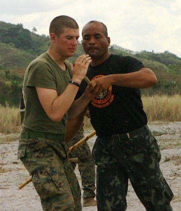 Lance Cpl. Taylor Jasper, a rifleman with Company E, Battalion Landing Team 2nd Battalion, 7th Marines (BLT 2/7), 31st Marine Expeditionary Unit (MEU), practices Pekithtirsia defense move with a Philippine martial arts instructor, March 13.  The martial arts class was part of bilateral training being conducted during exercise Balikatan 2010 (BK '10). (Official Marine Corps photo by Cpl. Michael A. Bianco)