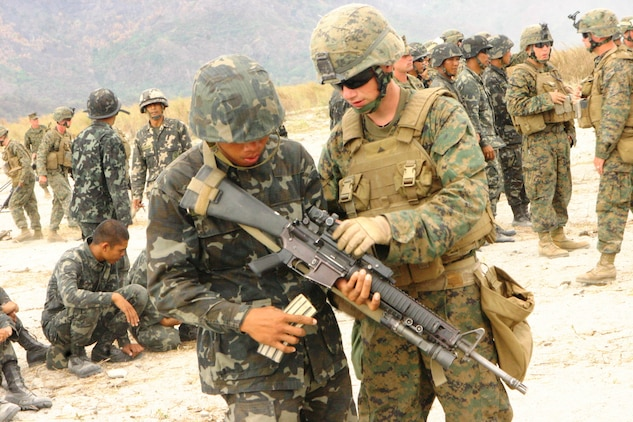 A Republic of the Philippines Marine learns about the M16 A4 service rifle from a U.S. Marine with Battalion Landing Team 2nd Battalion, 7th Marines (BLT 2/7), 31st Marine Expeditionary Unit (MEU), looks on during a small-arms shoot, March 13.  The small-arms shoot was part of bilateral training being conducted during exercise Balikatan 2010 (BK '10).
