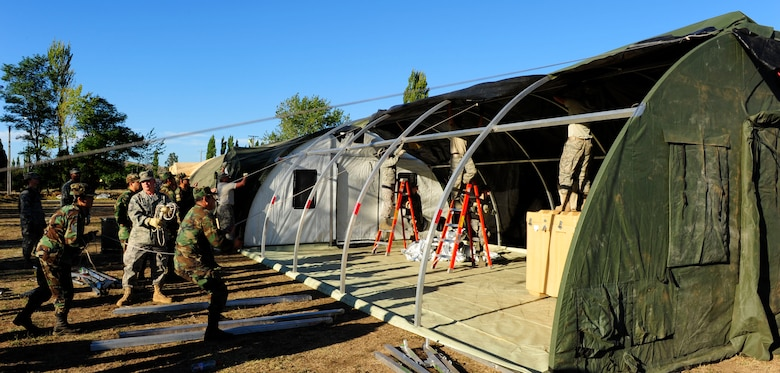 Airmen from an Air Force Expeditionary Medical Support team along with members of the Chilean army pull the roof over a mobile hospital March 12, in Angol, Chile. The EMEDS team is adding an additional operating room and three patient wards to the facility at the request of local Chilean medical officials. (U.S. Air Force photo/Senior Airman Tiffany Trojca)