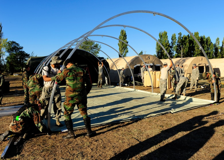 Chilean soldiers help Airmen from an Air Force Expeditionary Medical Support team erect an additional hospital tent March 12, in Angol, Chile. The additional tent will help meet the medical needs of the local community. (U.S. Air Force photo/Senior Airman TIffany Trojca)