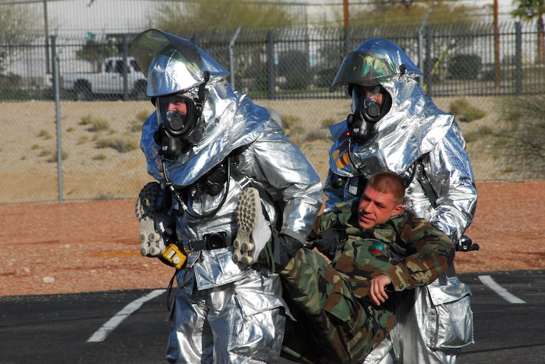 First responders from the base fire station carry an injured Guardsman to safety during a simulated accident March 12 as part of a compliance inspection exercise. The 162nd Fighter Wing at Tucson International Airport is hosting an inspection team from Air Education and Training Command March 10-16. (Air Force photo by Master Sgt. Dave Neve)