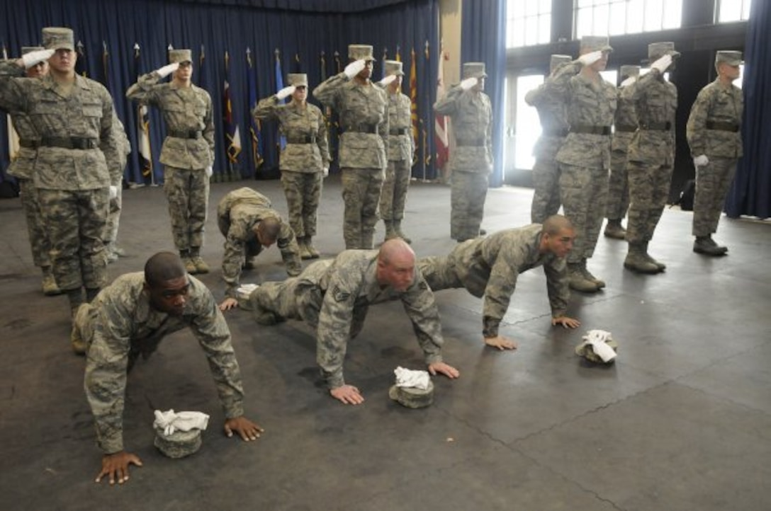 United States Air Force Honor Guard technical school trainees stay in the push-up position while the rest of the class holds their salute during practice, Feb. 22, 2010, inside the Honor Guard's C Hall on Bolling Air Force Base, D.C. While saluting, trainees are taught to not break bearing for any reason. As a form of discipline for mistakes, push-ups are a common practice among the honor guard technical school instructors. (U.S. Air Force photo by Senior Airman Marleah Miller)