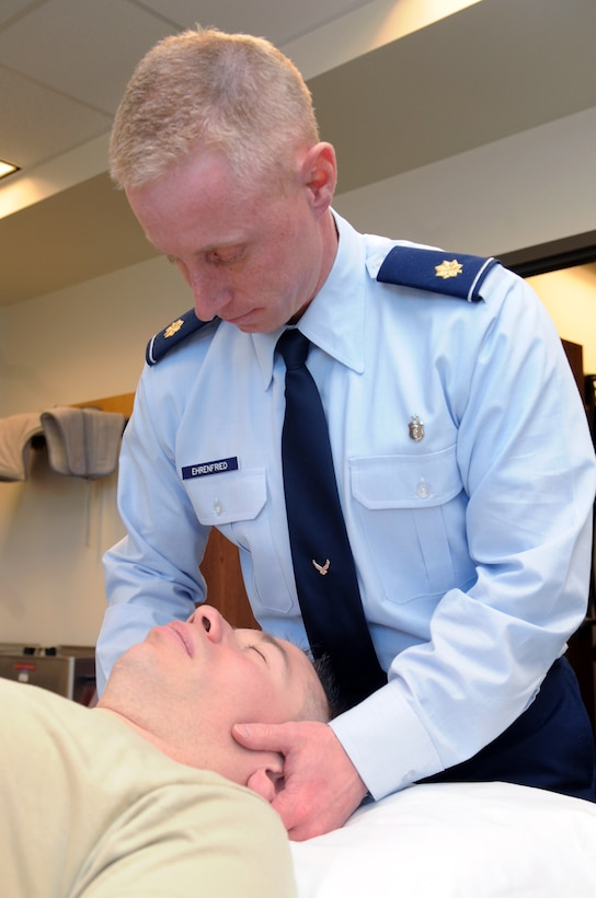 BUCKLEY AIR FORCE BASE, Colo. -- Maj. John Ehrenfried, 460th Medical Group head of physical therapy, performs a cervical and thoraic manipulation on 1st Lt. Kevin Hooker, 460th Medical Group Mental Health Clinic officer in charge March 16.  ( U.S. Photo by Airman 1st Class Marcy Glass )