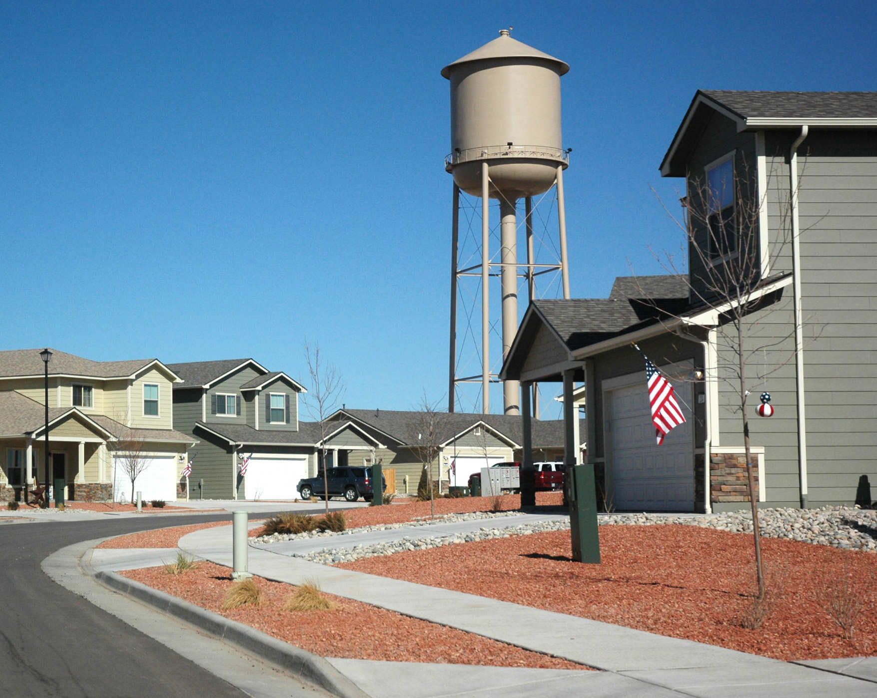 A water tower looms above a curving street of mostly two-story suburban-style homes in neutral colors with gravel front yards.
