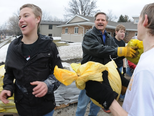N.D. Gov. John Hoeven joins a group of Fargo South High School students March 16 as they pass sandbags from pallets into backyards of houses along the Red River in south Fargo, N.D. The sandbags are being used to create flood barriers in an effort to protect homes from the rising water of the Red River. (DoD photo by Senior Master Sgt. David H. Lipp) (Released)