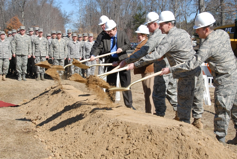 A formation of troops from the 103rd Maintenance Group watch as distinguished visitors heave the first shovel of dirt commemorating the official start of construction on the new Centralized Intermediate Repair Facility at Bradley Air National Guard base in East Granby, Conn.  March 6, 2010. Of the dignitaries are (from left) Robert Dwyer, project contractor, Cutter Enterprises; Jerry Otterson, project architect from Benham Companies L.L.C; Governor of Connecticut, M. Jodi Rell; Maj. Gen. Thaddeus J. Martin, the adjutant general for the state of Connecticut; Col. Frank N. Detorie, commander, 103rd Airlift Wing; and Lt. Col. Jerry McDonald, commander, 103rd Maintenance Group. The $8.3 million project will add 17,000 square feet of additional workspace and training areas for the repair and maintenance of the TF-34 engine. (U.S. Air Force photo by Tech. Sgt. Erin McNamara)