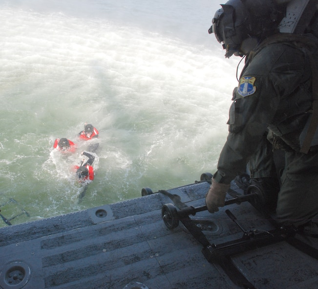 PATRICK AIR FORCE BASE, Fla. -  Air Force Reserve Tech. Sgt. Peter Pavenski, HH-60G Pave Hawk helicopter aerial gunner, 920th Rescue Wing here, throws the rope ladder to the awaiting pararescuemen below so they can climb into the hovering helicopter during a water training scenario being conducted in the Banana River near Patrick Air Force Base.  (U.S. Air Force photo/Staff Sgt. Leslie Kraushaar)
