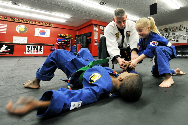 OFFUTT AIR FORCE BASE, Neb. - Gordon Taylor taps out when Tech. Sgt. Michael Munyon, with the 55th Security Forces Squadron, and Sophie Wolfe apply pressure to his wrist during a hapkido class at an Omaha dojang March 12. Sergeant Munyon currently holds a 5th degree black belt in Taekwondo and a 2nd degree black belt in Hapkido, another form of Korean martial arts. He was recently inducted into the Masters Hall of Fame.