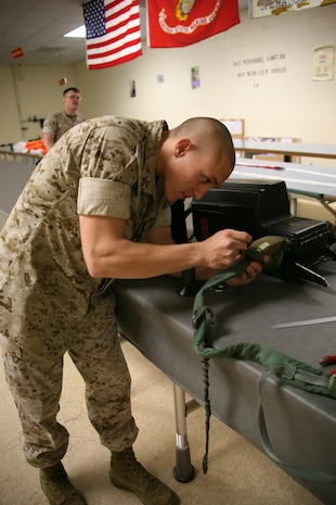 Lance Cpl. Jacob W. Grohman, a flight equipment technician with Marine Aviation Logistics Squadron 14's aviation life support system section, makes the final repairs on a parachute. Parachute riggers spend anywhere from four hours to a full day repairing parachutes for the squadrons of 2nd Marine Aircraft Wing.