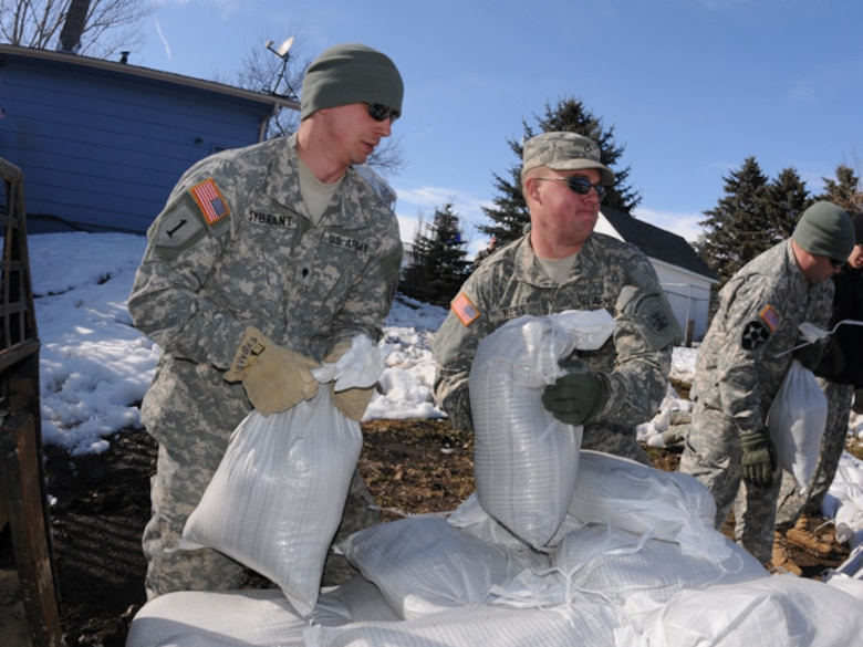 Spc. Tim Sybrant, of the 817th Engineer Sapper Company (Jamestown, N.D.), left, passes sandbags to Pfc. Scott Ness, of the 188th Engineer Company (Wahpeton, N.D.), March 17, in the backyard of Konny Zins and her husband, Sgt. Darin Zins, who is currently deployed to Kosovo and can do little more than empathize with his family during Skype calls from half a world away. He serves with the 231st Maneuver Task Force, part of the NATO peacekeeping forces in Kosovo Force 12. The Soldiers are building a sandbag flood barrier to hold back rising water from the Sheyenne River. (DoD photo by Senior Master Sgt. David H. Lipp) (Released)