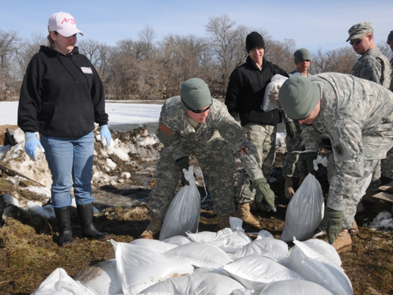 Konny Zins, left, looks on as North Dakota Army National Guard members build a sandbag flood barrier in her backyard March 17, just outside of Lisbon, N.D.  Her husband, Darin, is a sergeant in the North Dakota Army National Guard and is currently deployed to Kosovo as part of the NATO peacekeeping forces in Kosovo Force 12.  In Darin's absence, the Guardsmen came to his aid to help protect the Zins' home from the rising floodwaters. (DoD photo by Senior Master Sgt. David H. Lipp) (Released)
