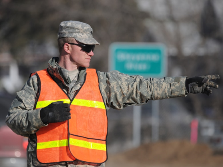 Spc. Danny Gross, of the 191st Military Police Company, directs traffic at a busy intersection March 17 in Lisbon, N.D.  Gross, of Enderlin, N.D., is operating a North Dakota National Guard traffic control point (TCP) in order to allow dump trucks carrying dike building clay to arrive at flood fighting locations in a timely manner.