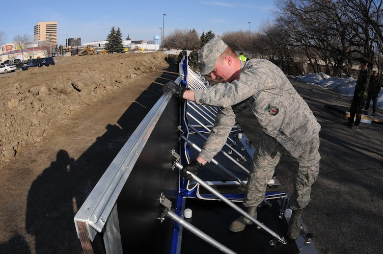 Airman 1st Class Casey Pritchard, of the 119th Civil Engineer Squadron, assembles a section of AquaFence March 17 near NP Avenue in Fargo, N.D. The fence is being installed by the North Dakota Air National Guard as a test flood barrier for the City of Fargo to see if it might be effective for use in future flood protection.  (DoD photo by Senior Master Sgt. David H. Lipp) (Released)