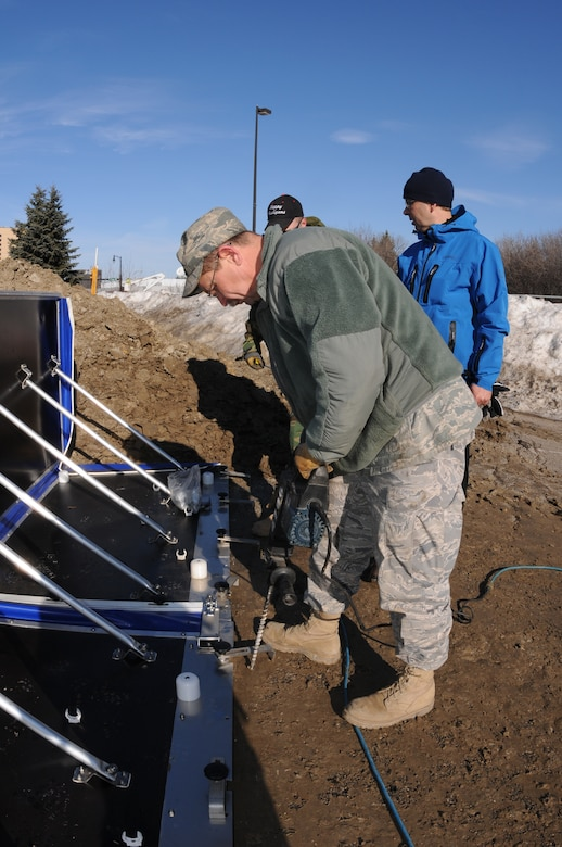 Senior Master Sgt. Scott Wagner, of the 119th Civil Engineer Squadron, drills a hole in pavement to secure an experimental AquaFence in place March 17 in Fargo, N.D. The AquaFence is being installed by the North Dakota Air National Guard for the City of Fargo as a test flood barrier to see if it might be effective for use in future flood protection.  (DoD photo by Senior Master Sgt. David H. Lipp) (Released)