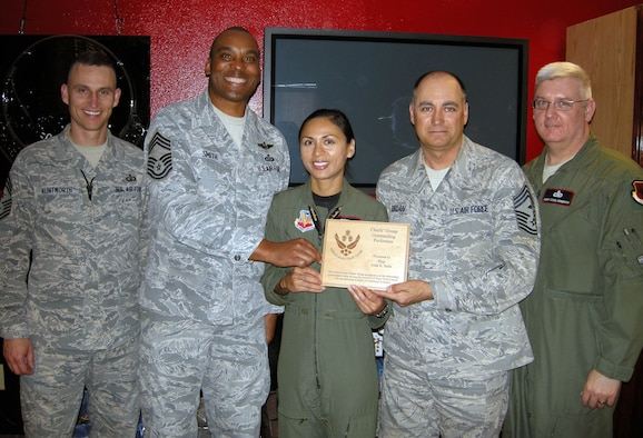 Staff Sgt. Solis (center), received an Excellence in Action award March 3. The award is presented monthly by the Chief's Group to deserving Airmen who have gone above and beyond the normal call of duty. (U.S. Air Force photo/Staff Sgt. Alice Moore)
