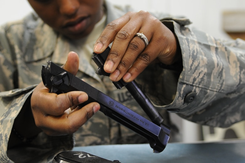 WHITEMAN AIR FORCE BASE, Mo. -  A 509th Security Forces Squadron Airman disassembles an M-9 pistol during combat arms training here, March 16, 2010.(U.S. Air Force photo by Airman 1st Class Carlin Leslie)(Released)