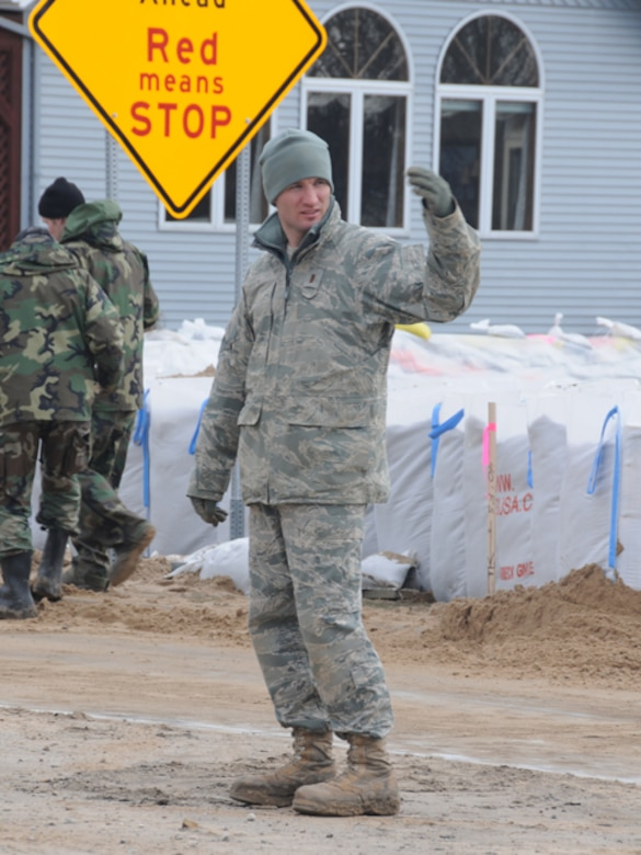 2nd Lt. Shawn Muehler, of the North Dakota Air National Guard, directs a flood fighting equipment into place March 18, Fargo, N.D.  Muehler is part of team that is filling and placing large sandbags into place to create a flood barrier from the rising water of the Red River.