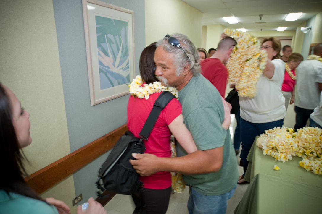 """Colorado Air National Guard personnel of the 140th Medical Group, Buckley Air Force Base are greeted with a lei and a hug by Rodney and Denise, staff of the Kahuku Medical Center, Kahuku, Hawaii, March 14, 2010.  More than 60 Guardsmen attended a familiarization briefing to learn about the various aspects of the Hawaiian culture before beginning their work as part of E Malama Kakou (translated from Hawaiian as """"to care for all""""), an Innovative Readiness Training Program. (U.S. Air Force photo/Master Sgt. John Nimmo, Sr.) (RELEASED)"""