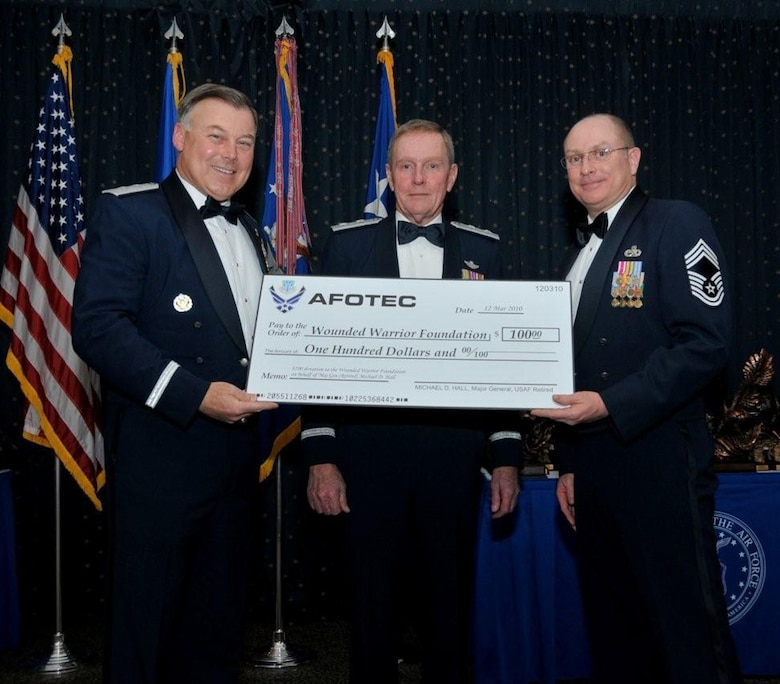 Air Force Operational Test and Evaluation Center Commander Maj. Gen. Stephen T. Sargeant (left) presents Maj. Gen. Michael D. Hall (retired) a donation to the Wounded Warrior Foundation in his name in appreciation for being a guest speaker at the March 26, 2009 AFOTEC Annual Awards Banquet. AFOTEC Chief Enlisted Manager CMSgt. Kelly Branscom (right) assists in the presentation. More than 185 AFOTEC member were recognized as outstanding performers for 2009.