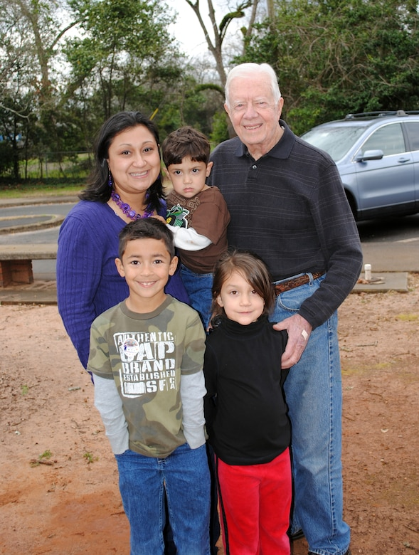 Yvette Nunez and her children (clockwise) Noah, Teegan and Lola pause for a photo with President Jimmy Carter during the Airman and Family Readiness Center train trip to Plains. U.S. Air Force photo by  Tech. Sgt. Vann Miller