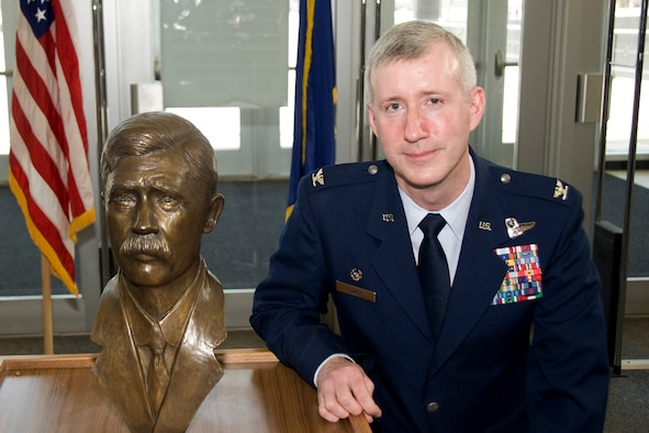 """Col. David Lange poses next to a bust of his great, great uncle, Charlie Taylor, in the Air Force Academy's McDermott Library March 2, 2010. Mr. Taylor built the first aircraft engine used by the Wright Brothers and helped the brothers prepare the """"Military Flyer"""" for demonstration to the U.S. Army at Fort Myer, Va. Colonel Lange is the air officer commanding for Cadet Group 2. (U.S. Air Force photo/Bill Evans)"""
