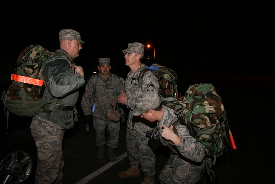 ROBINS AIR FORCE BASE, Ga. - Lt. Col. Todd Schug, 52nd Combat Communications Squadron and ruck march commander, (left) and Staff Sgt. Rome Reiswig, 52nd CBCS Customer Support Squadron non-commissioned officer in charge, talk with Chief Master Sgt. Shawn Coyle, 52nd CBCS superintendent, about the ruck march route while 2nd Lt. Patrick Beville prepares his ruck pack. The route would take more than 30 members of the 689th Combat Communications Wing across six miles of Robins' roadways and woodlands March 15, in honor of Chief Coyle's retirement March 19. (U.S. Air Force Photo/2nd Lt. Joel Cooke)