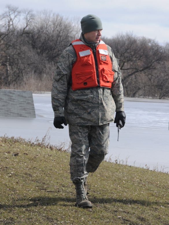 Staff Sgt. James Pollard, of the 119th Logistics Readiness Squadron, patrols a flood dike March 19 along the Red River in Fargo, N.D. The North Dakota Air National Guard member was tasked with keeping sightseers off of the flood dikes and also monitoring the clay dikes for possible trouble spots that could become breaches in the dike if they are left unchecked. The roof of a submerged garage can be seen in the water behind Pollard as we walks at the waters' edge.    (DoD photo by Senior Master Sgt. David H. Lipp) (Released)