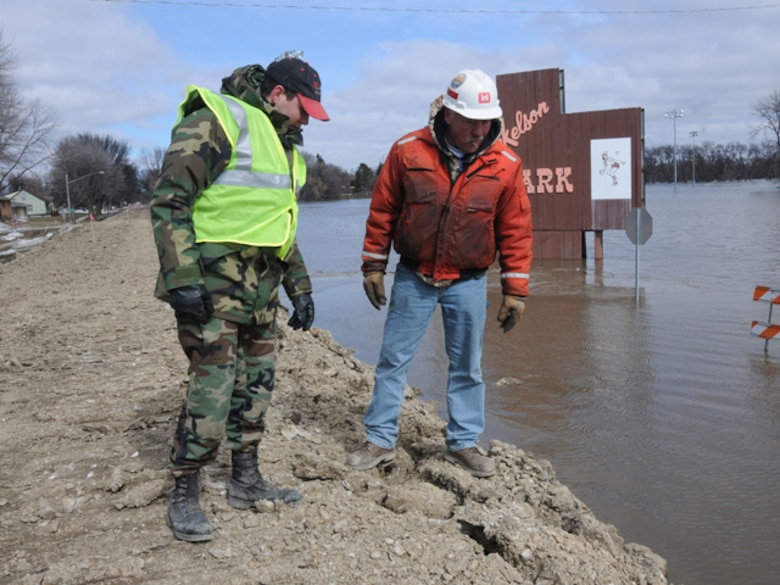 Staff Sgt. Wayne Baumbach, of the 119th Communications Flight, points out a possible problem area in a clay dike to Kevin Ressie, of the U.S. Army Corp of Engineer (St. Paul office), March 19, Fargo, N.D.  Baumbach is a North Dakota Air National Guard flood dike walker, who is tasked with watching the flood dikes for possible problems and also to keep people from climbing up on the dikes. Ressie is responsible for construction and maintenance of the dikes. (DoD photo by Senior Master Sgt. David H. Lipp) (Released)