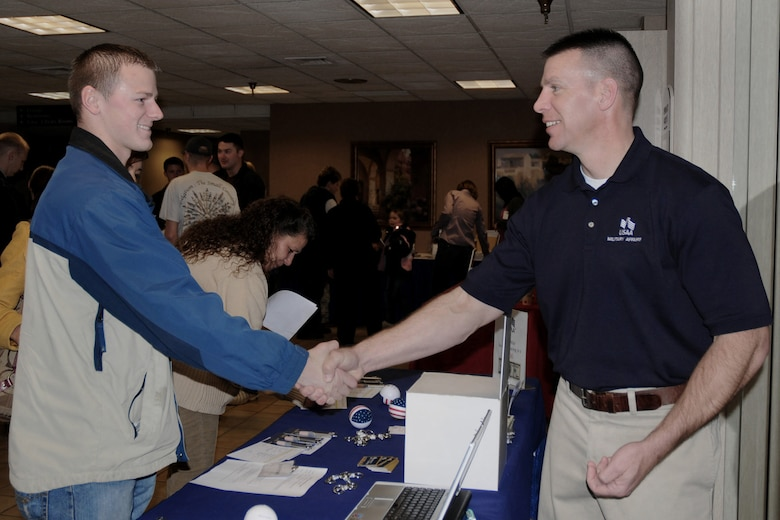 Staff Sgt. Joshua Brady (left) receives a coin from USAA Military Affairs Representative Michael Evans (right) at the Yellow Ribbon Event held at the Holiday Inn Airport in Des Moines, Iowa on March 6, 2010.  The coin is being presented to Sgt. Brady as a ?thank you? for his service and time spent overseas on a recent deployment.  (US Air Force photo/Staff Sgt. Linda E. Kephart)(Released)