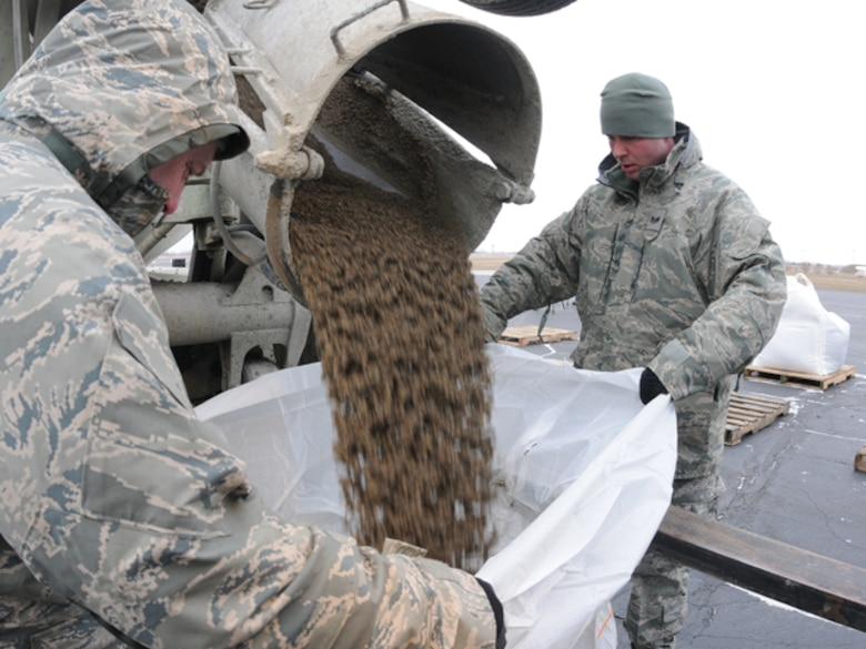 Tech Sgt. Kevin Reinhardt, left, and Staff Sgt. Anthony Salquist, both of the 119th Logistics Readiness Squadron, fill one-ton sandbags with sand from a cement truck, in preparation for use in flood fighting operations March 19 at the North Dakota Air National Guard, Fargo, N.D.  The large sandbags are being readied for UH-60 helicopter sling-load operations, should they be necessary in emergency battling rising flood waters anywhere in eastern North Dakota.