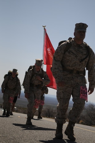 """Yuma-based Marines Pfc. Adrian Velasquez, right, Lance Cpl. Shane Fields and Lance Cpl. Anthony Scott march up Mineral Hill during the 2010 Bataan Memorial Death March at White Sands Missile Range, N.M., March 21, 2010. The annual 26.2-mile march is held in memory of the nearly 75,000 American and Filipino service members forced to march across 90 miles of the Philippine Bataan peninsula with limited rations and harsh heat while interned by the Japanese in 1942. Mineral Hill, nine miles into the course, took the marchers more than a mile above sea level. """"I don't think anyone can prepare themselves for this,"""" said Scott. At least nine Marines from the Marine Corps Air Station in Yuma, Ariz., participated in the event."""